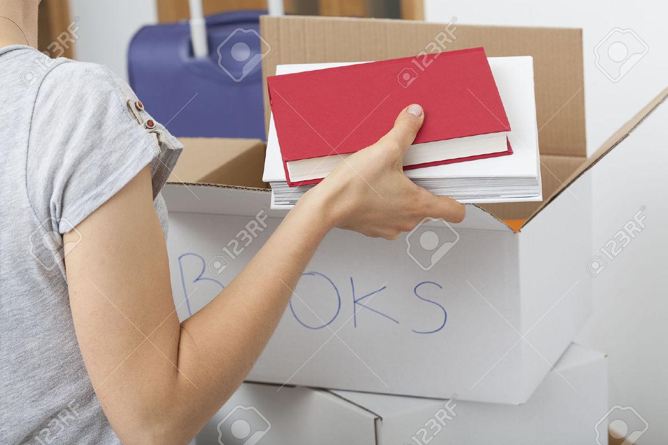26312839-Chica-organizar-diferentes-tipos-de-libros-en-cajas-descriptos-Foto-de-archivo